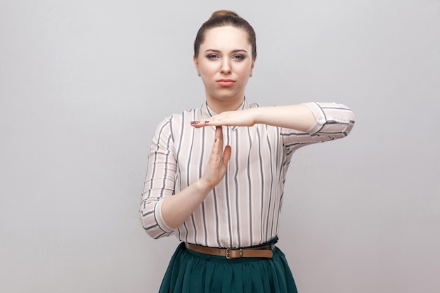 I need more time. beautiful young woman in striped shirt and green skirt with makeup and collected ban hairstyle, standing with timeout gesture. indoor studio shot, isolated on grey background.