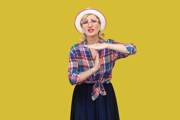 私にはもっと時間が必要です。時間のジェスチャーで立っている帽子と眼鏡とカジュアルなスタイルで希望に満ちたモダンでスタイリッシュな成熟した女性の肖像画とタイムアウトを作成したいと考えています。黄色の背景に分離されたスタジオショット