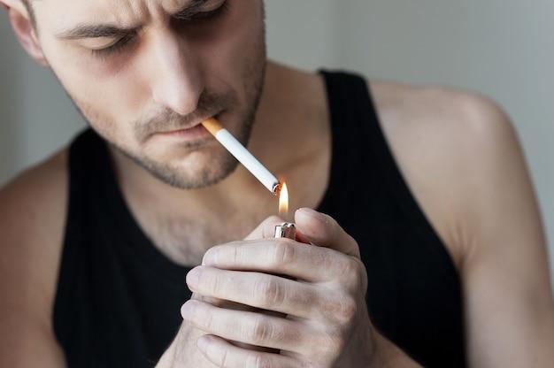 담배가 한 개 더 필요합니다. 담배를 피우는 젊은 남자의 클로즈업