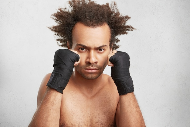 I need only victory. confident fighter with serious expression and taped hands look angrily at opponent