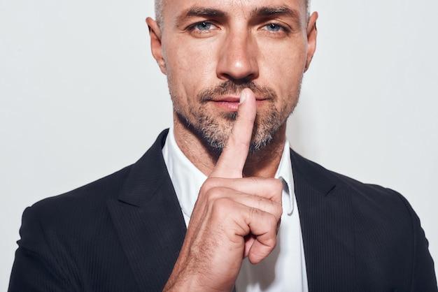 沈黙が必要です。カメラを見て、灰色の背景に立っている間唇に指を保持しているひげを生やした実業家の肖像画を閉じます。静けさ。働く。仕事