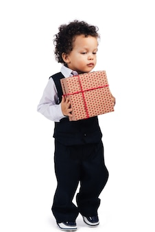 I need some nice place to hide my gift! little african baby boy holding gift box while walking against white background