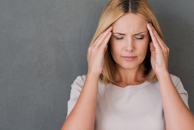 鎮痛剤が必要です。額に触れて目を閉じたまま落ち込んでいる成熟した女性