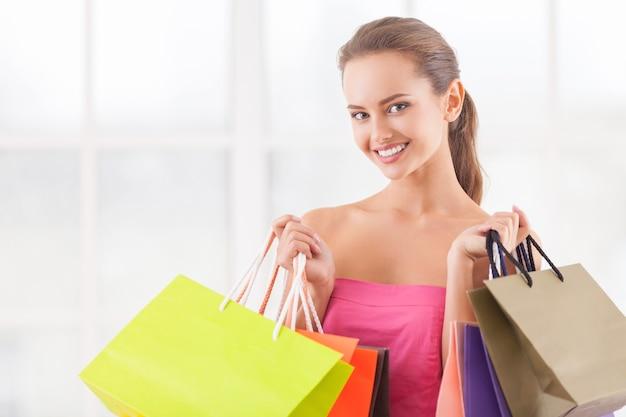 小売療法が必要です。ショッピングバッグを持ってカメラに笑顔の魅力的な若い女性