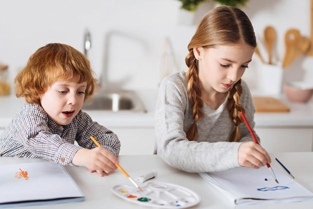 그 그늘이 필요 해요. 햇볕이 잘 드는 방의 테이블에 앉아 수채화를 사용하여 재미있는 그림을 그리는 호기심 많은 재능있는 활동적인 아이들