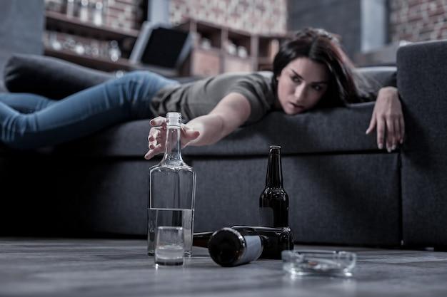 Мне нужен этот напиток. селективный фокус полупустой бутылки водки, которую принимает пьяная молодая женщина во время похмелья
