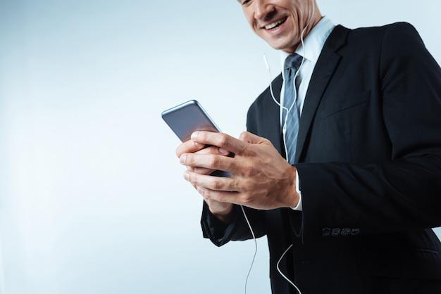 Мне нужно расслабиться. крупный план современного смартфона, находящегося в руках красивого приятного человека во время прослушивания музыки