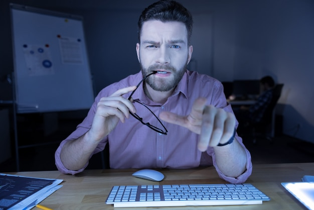 私は休息する必要があります。コンピューターの画面を見ながら眼鏡を持って噛んでいる素敵な神経質な疲れたit男