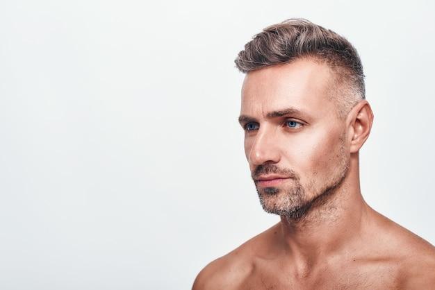 私は剃るする必要があります。灰色の背景に立っている間脇を見て無精ひげとハンサムでセクシーな男の側面図。男性の美しさ。スキンケア