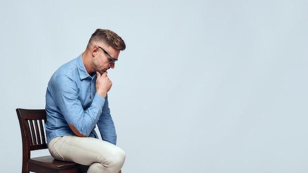 私は考える必要があります。灰色の背景に椅子に座っている間彼のあごに触れるカジュアルな服とサングラスのハンサムなひげを生やした男の側面図。思考プロセス。男性の美しさ。スタジオショット Premium写真