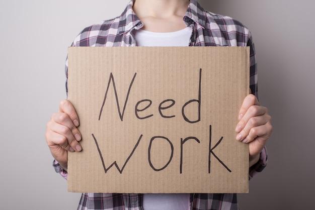 Мне нужна концепция работы. обрезанное крупным планом фото несчастной женщины, держащей вывеску с текстом, изолированным на сером фоне