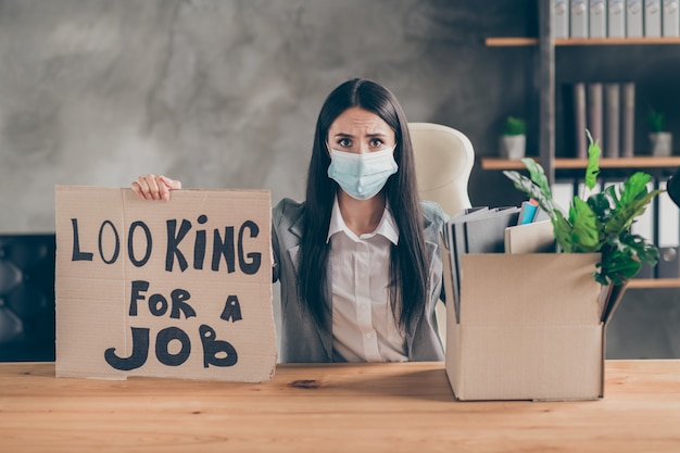 I need work. frustrated stressed girl ceo marketer banker sit table desk lose job company covid economics crisis show cardboard text box wear medical mask blazer jacket in workplace