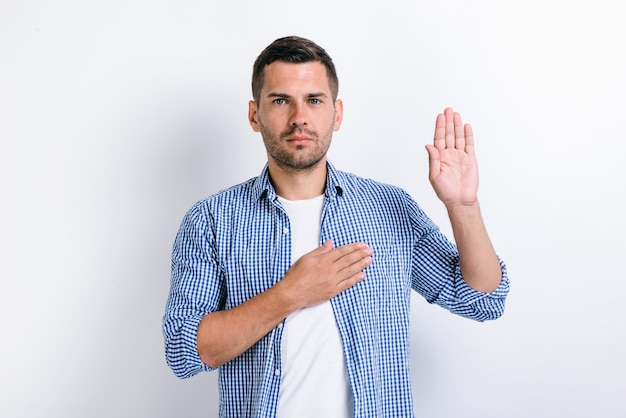 I promise to tell truth! portrait of honest responsible bearded man standing raising hand and saying swear, making loyalty oath, pledging allegiance. indoor studio shot, white background