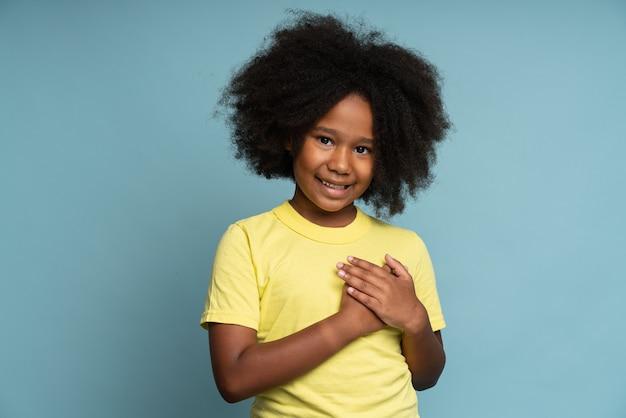 정직할 것을 약속드립니다. 그녀의 마음에 그녀의 손을 잡고 행복 책임 어린 소녀의 초상화. 진실을 말하겠다고 맹세하는 아이. 파란색 배경에 고립 된 스튜디오 촬영