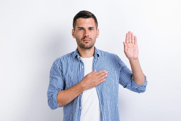 진실을 말할 것을 약속합니다! 수염을 기른 정직한 남자의 초상화는 손을 들고 맹세하고 충성 맹세를 하고 충성을 맹세합니다. 실내 스튜디오 촬영, 흰색 배경