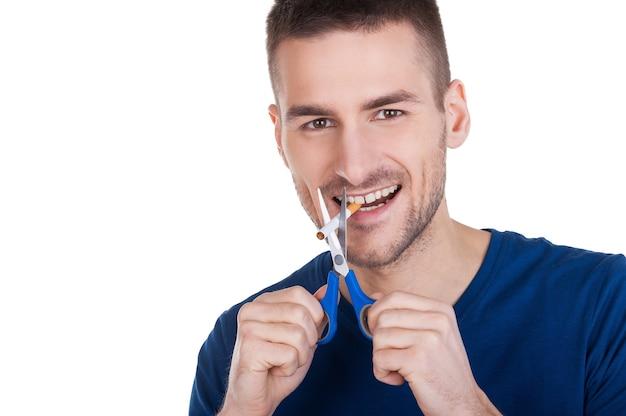 나는 담배를 끊었다! 흰색 배경에 격리된 채 담배 근처에 가위를 들고 있는 쾌활한 청년