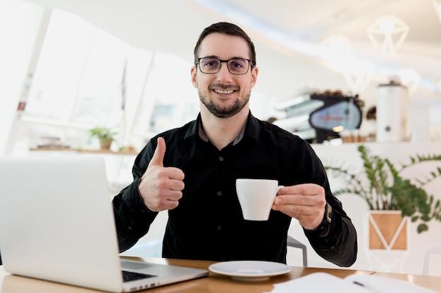 私はこのコーヒーが本当に好きです!グラスと黒のシャツを着た魅力的な男性は、フラットホワイトのカップを保持し、笑顔で親指を立てます。背景に明るいコーヒーショップのインテリア。コーヒーは集中力を高めます。