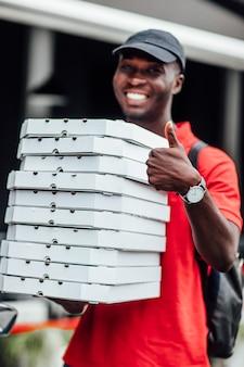 この美味しいピザを食べることをお勧めします!陽気なアフリカの忙しい男性の宅配便は、段ボールの容器に食欲をそそるファーストフードを届け、親指を立て続け、ジェスチャーのように見せ、原付を運転します。