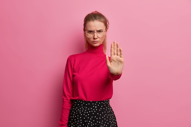 I said no. serious angry girl keeps palm forward, makes refusal gesture, rejects something, asks not bother her, prohibits action, frowns in displeasure, extends arm in stop sign