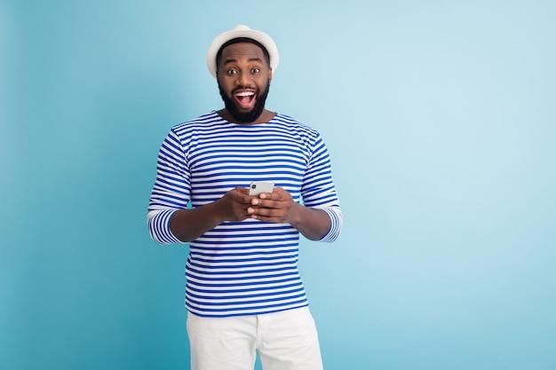 海が見える!面白い暗い肌の男の旅行者の良い気分の写真は、電話アプリのチャットの友人が白い日よけ帽を身に着けているストライプのセーラーシャツのショートパンツ孤立した青い色の壁を保持します