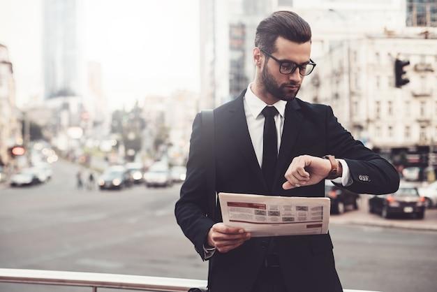 私は間に合うはずです。新聞を保持している完全なスーツで自信を持って若い男