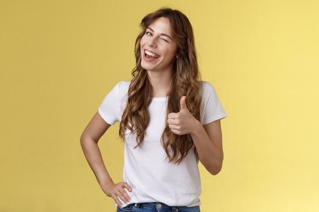 私はあなたたちの幸運をサポートします。幸せな陽気な生意気な魅力的な女の子のウィンクの承認は、親指を立てて笑顔で広く満足している素晴らしいパーティーを祝福する友人のよくやった黄色の背景のような