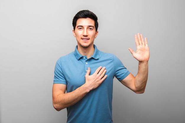 Клянусь. красивый молодой человек в синей рубашке с рукой на груди, давая овес.