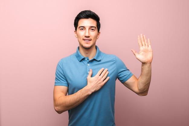 Клянусь. красивый молодой человек с нейтральной улыбкой в синей рубашке поло с рукой на груди, давая клятву.