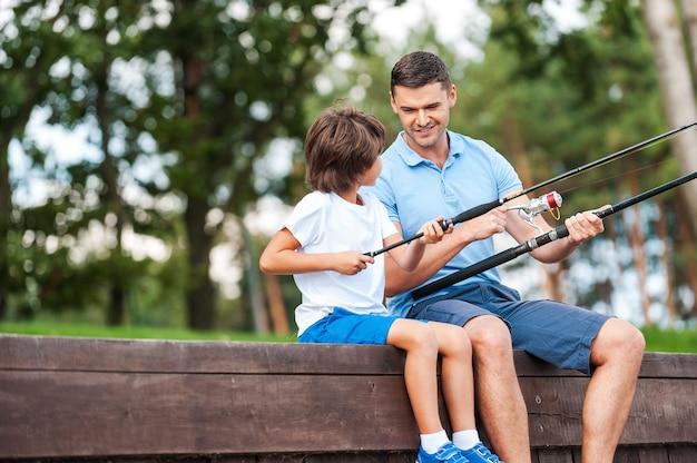 Все дело в прямом угле. веселый отец и сын на рыбалке, сидя на набережной