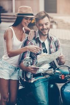 私たちはここにいると思います!一緒にスクーターに座って、女性がそれを指して笑っている間地図を調べる美しい若い愛情のあるカップル
