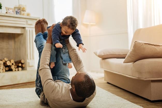 私はあなたを大切にしています。床に横たわって子供を腕に抱きながら幸せな幼い息子と遊んでいる元気な黒髪のひげを生やしたアフリカ系アメリカ人の男
