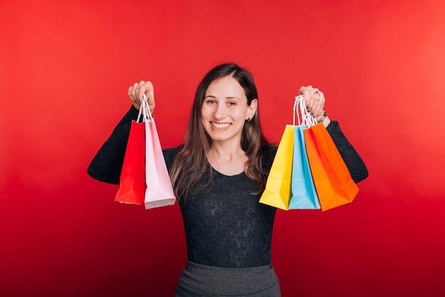 새로운 것들이 있습니다. 젊은 여자는 몇 가지 화려한 쇼핑 가방을 들고 카메라에 미소.
