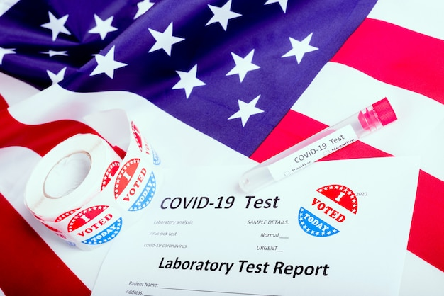 I voted sticker on the american flag and some test tubes of covid19 during the election time in the united states.