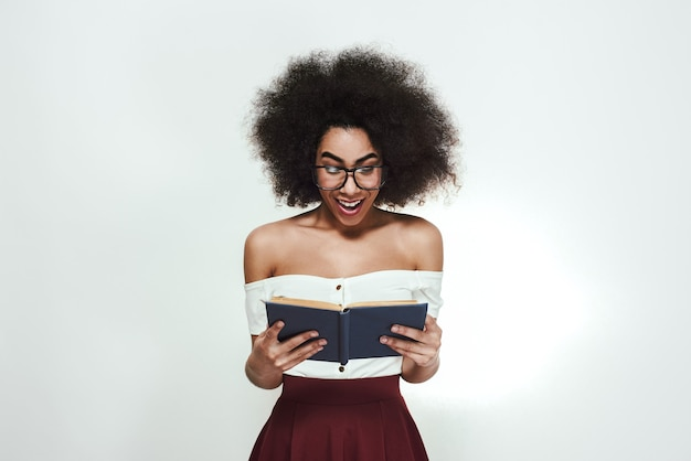 I want to know everything excited young woman in eyewear reading the book with opened