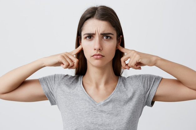 I don't want to listen to you anymore. young beautiful unhappy caucasian girl with long brown hair in gray shirt clothing ears with hands,  with tired and sad expression