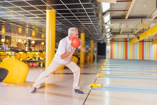 Я хочу нанести удар. хороший активный мужчина держит мяч, целится в кегли