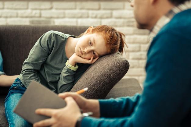 休みたい。疲れを感じながらソファに寄りかかって悲しい不幸な少女