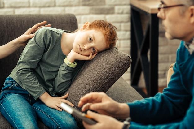 寝たい。心理学者の話を聞いている間、非常に疲れていると感じている落ち込んでいる赤い髪の少女