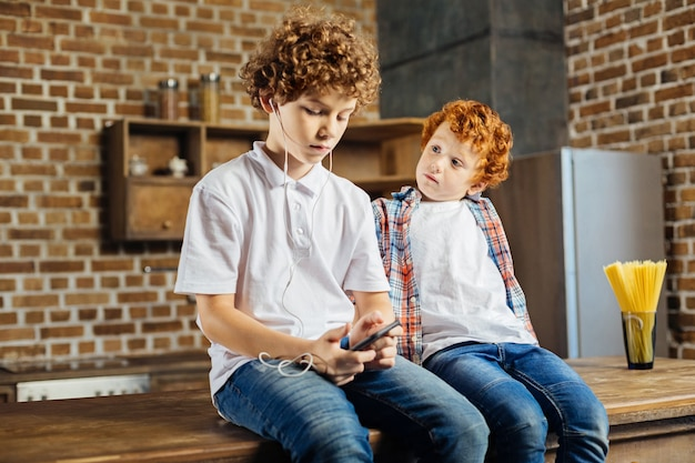 내가 너무 할. 호기심 어린 소년은 집에서 부엌 섬에 앉아있는 동안 이어폰을 착용하고 음악을 듣고 진지한 동생을주의 깊게보고 있습니다.