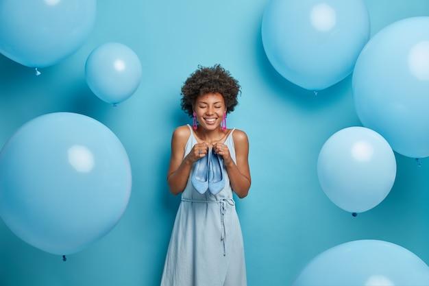 Voglio indossare queste scarpe blu col tacco alto. la donna felice sceglie il miglior vestito del colore preferito dal guardaroba, prova nuovi vestiti e calzature, soddisfatta dopo aver visitato una boutique di lusso. moda femminile