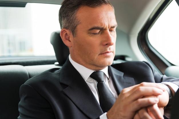 나는 시간에있을 것이다. 자동차 뒷좌석에 앉아 시계를 바라보는 자신감 있는 성숙한 사업가