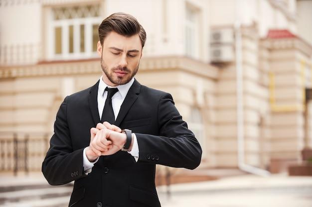 나는 시간에있을 것이다. 거리에 서 있는 동안 그의 시계를 보고 formalwear에서 잘 생긴 젊은 남자