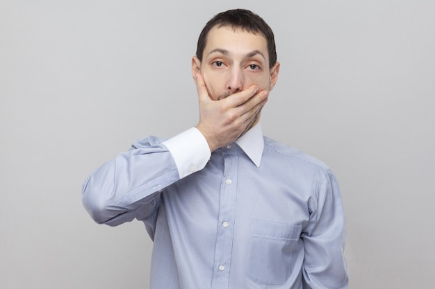 나는 조용히 할 것이다. 큰 눈으로 카메라를 보고 입을 가리고 서 있는 고전적인 파란색 셔츠에 충격을 받은 잘생긴 강모 사업가. 실내 스튜디오 촬영, 회색 배경 copyspace에 격리.