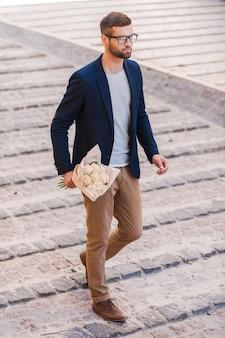 私は間に合うでしょう。通りを歩きながら花の花束を保持しているスマートカジュアルウェアのハンサムな若い男の全長