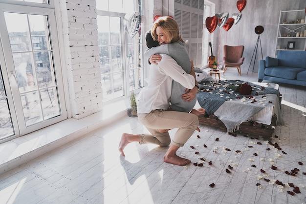 나는 당신과 결혼 할 것입니다! 주위에 장미 꽃잎과 함께 침실에 서있는 동안 포용하고 웃는 아름다운 젊은 부부