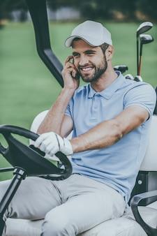 Встретимся на зеленом! красивый молодой улыбающийся человек за рулем тележки для гольфа и разговаривает по мобильному телефону