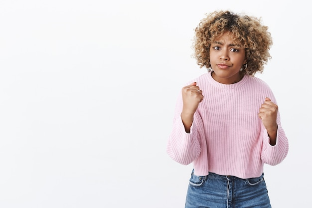 I will show you, come closer. portrait of angry and cute african american blonde in sweater frowning offended and sulking raising fists in boxing pose wanting punch and fight over white wall