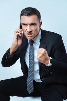 보여 드릴게요. 불행한 좋은 성인 남자가 전화로 이야기하고 그의 대담 자에게 화를 내면서 주먹을 움켜 쥐고