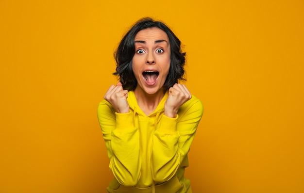 勝った!黄色いパーカーを着て、彼女の成功と陽気に叫ぶことを楽しんでいる、エネルギーに満ちた魅力的な嬉しい驚きの女の子