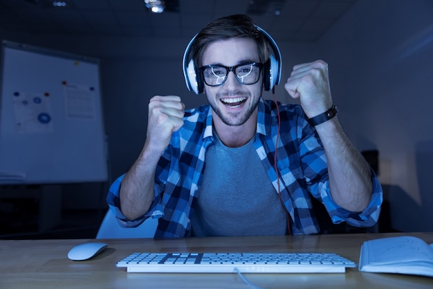 내가이 겄어. 쾌활한 기쁘게 수염을 기른 남자가 주먹을 움켜 쥐고 컴퓨터 게임에서 승리하는 동안 웃고